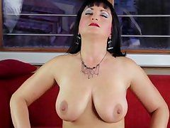 milf dark brown with round whoppers stroking on the sofa